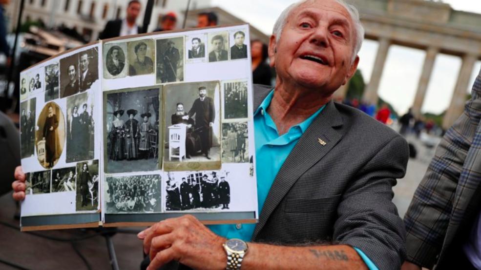 In 2017 in front of Berlin's Brandenburg Gate, Holocaust survivor Morris Dan holds photos of his family. Photo:  Fabrizio Bensch/Reuters