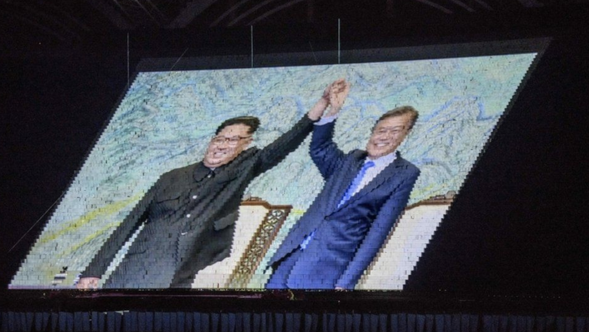 "An image of North Korean leader Kim Jong-un (left) and his South Korean counterpart Moon Jae-in at a prior summit was also rendered by a ""human pixel"" screen at the Games. Photo:  AFP ."