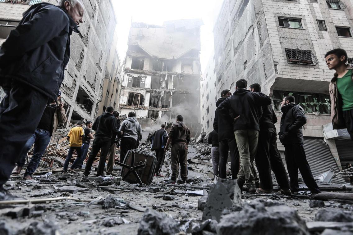 Palestinians gather in front of damaged buildings in Gaza City following Israeli air strikes. Credits: AFP