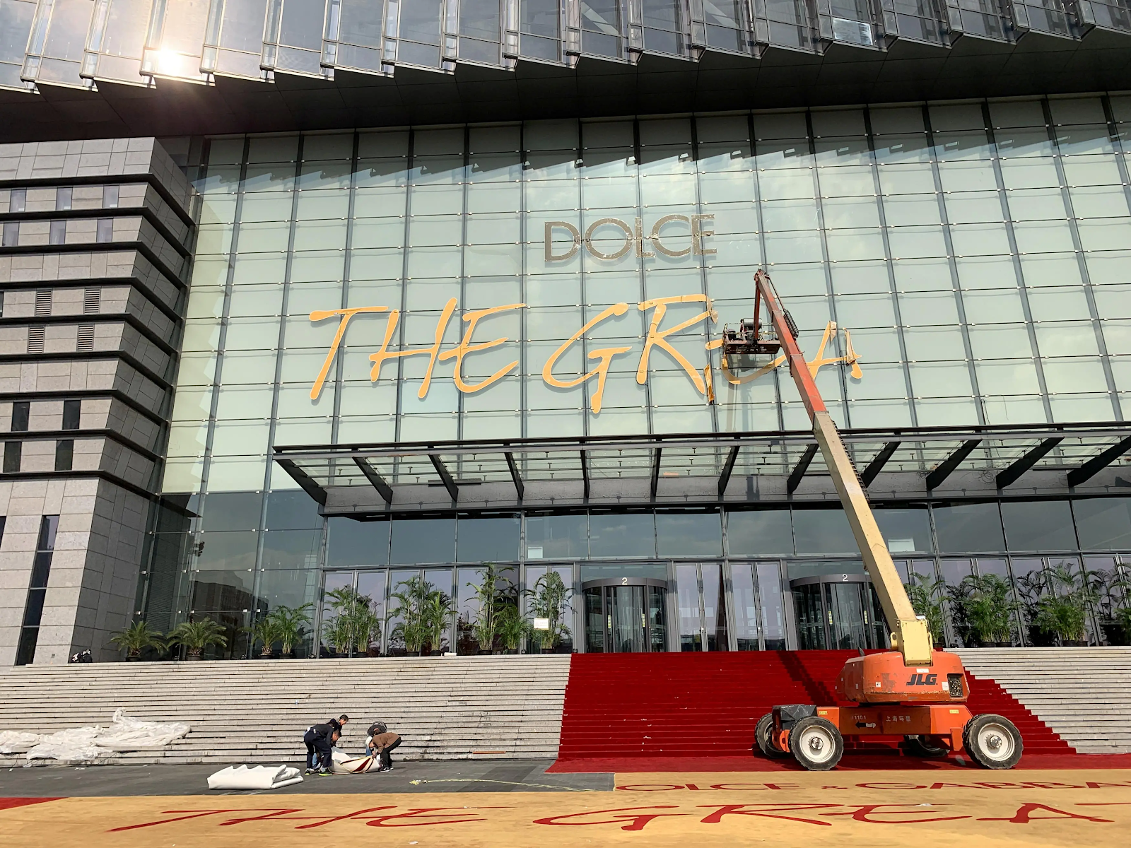 "Workers remove a sign reading ""Dolce and Gabbana The Great Show"" at the Shanghai Expo Center on Nov. 22 after the fashion show was abruptly cancelled the day prior. Credit:  Reuters"