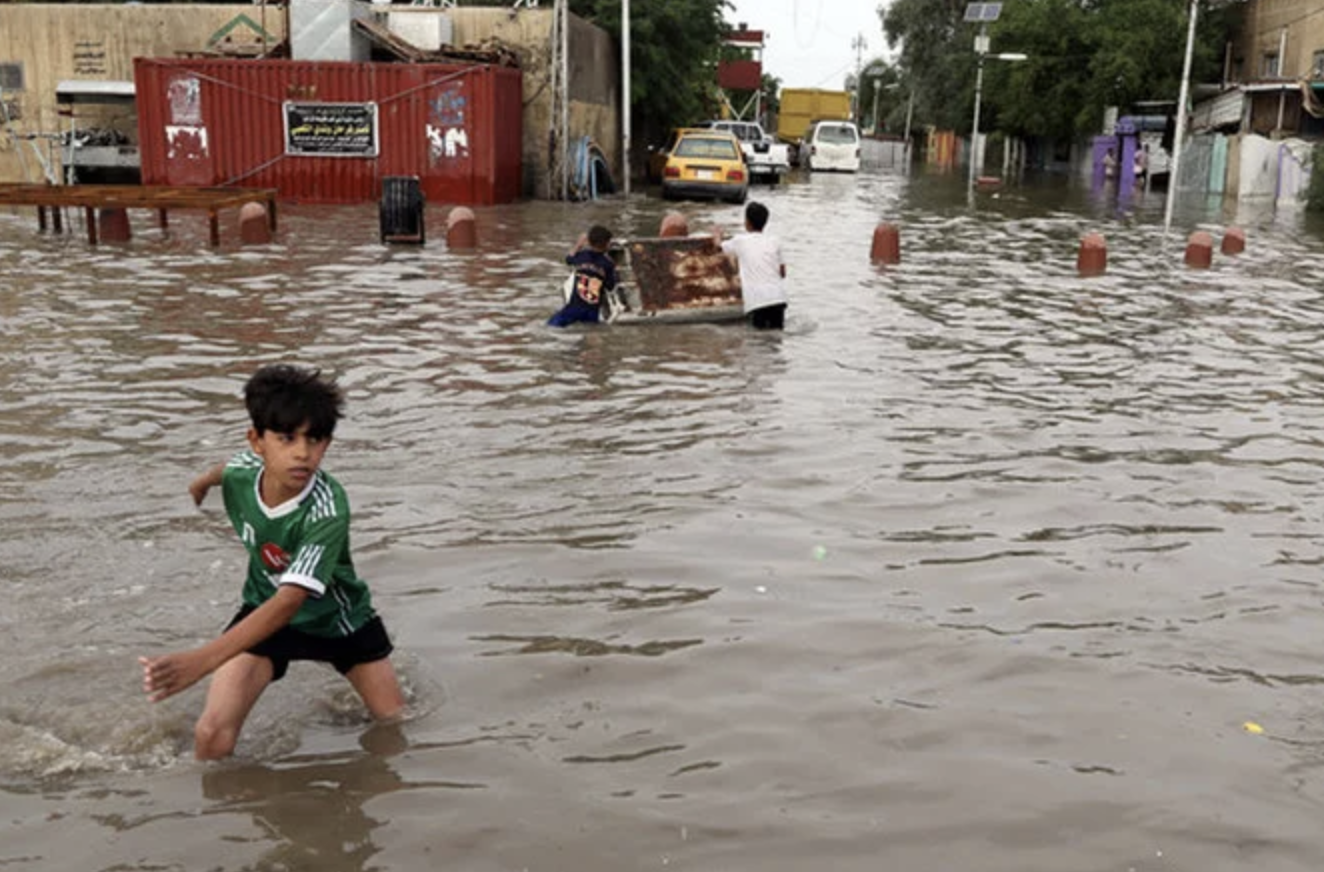A boy walks through a flooded area of Baghdad, Iraq. Credit : Associated Press