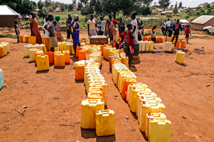 Residents of Kiryandongo refugee settlement camp in central Uganda line up at a borehole to receive water. Photo: Bill Oketch /  AllAfrica .