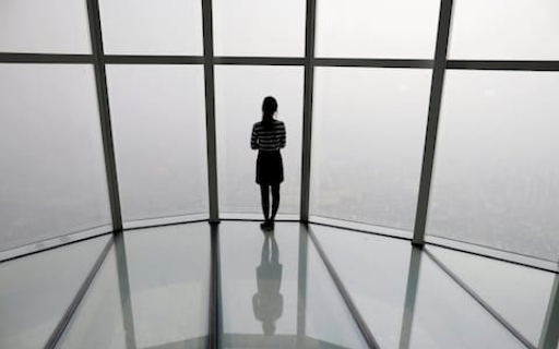 A woman looks out over the barely visible Seoul skyline. Photo:  Kim Hong-ji/Reuters