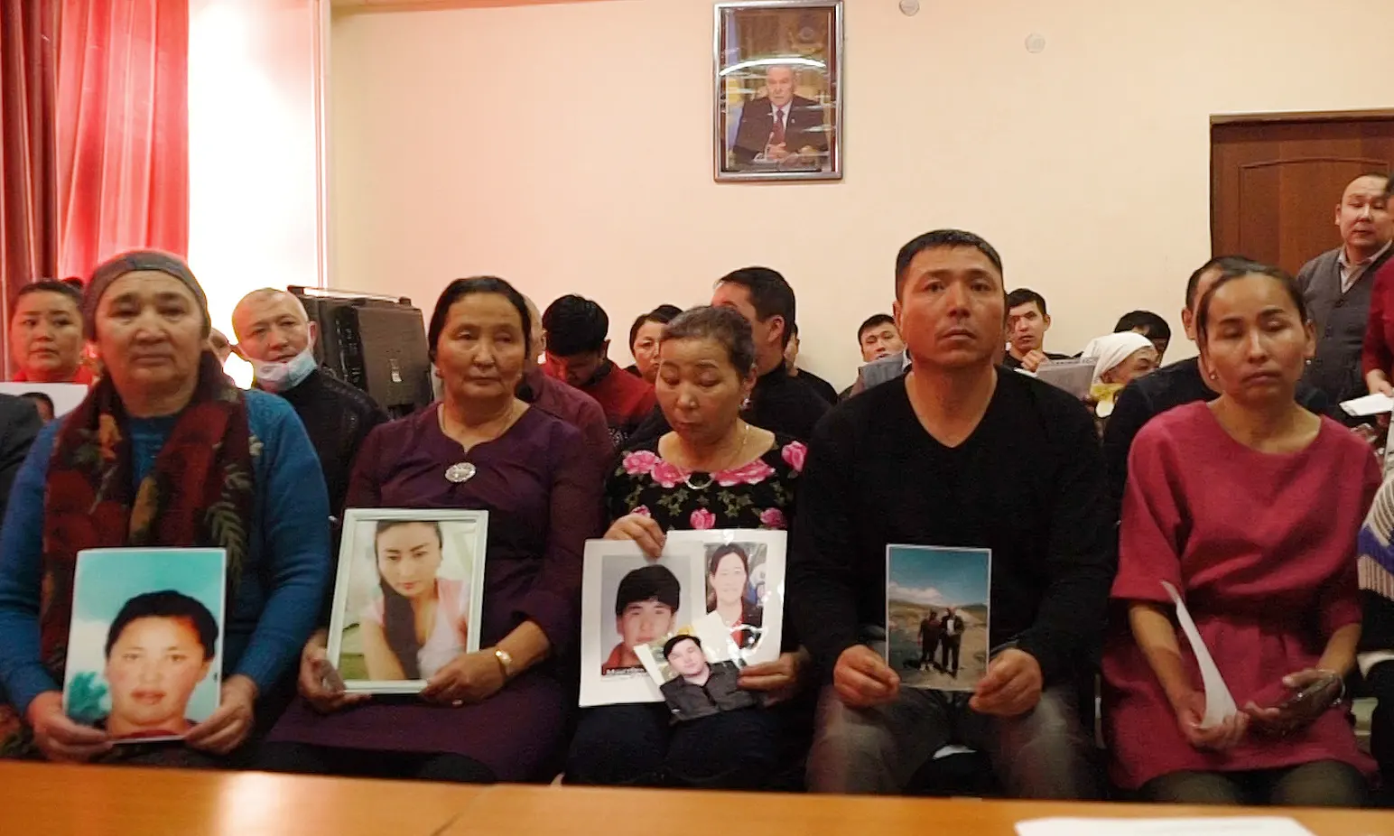 Kazakh relatives hold up photos of missing relatives in this image dated to December. Photo:  Dake Kang/AP