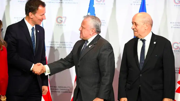 U.S. Deputy Secretary of State John Sullivan, attending the summit in place of U.S. Secretary of State Mike Pompeo, shakes hands with U.K. Foreign Secretary Jeremy Hunt as France Foreign Minister Jean-Yves Le Drian stands by. Photo:  AFP