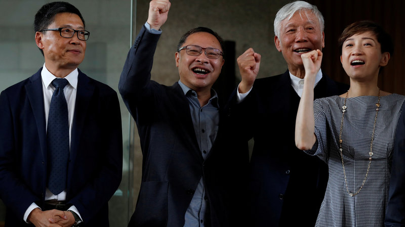 From left to right: Occupy Central founder Chan Kin-man, Benny Tai, and Chu Yiu-ming as well as Tanya Chan chant slogans with the crowd of supporters after their trial, which convicted them all on charges of public nuisance. Photo:  Tyrone Siu/Reuters