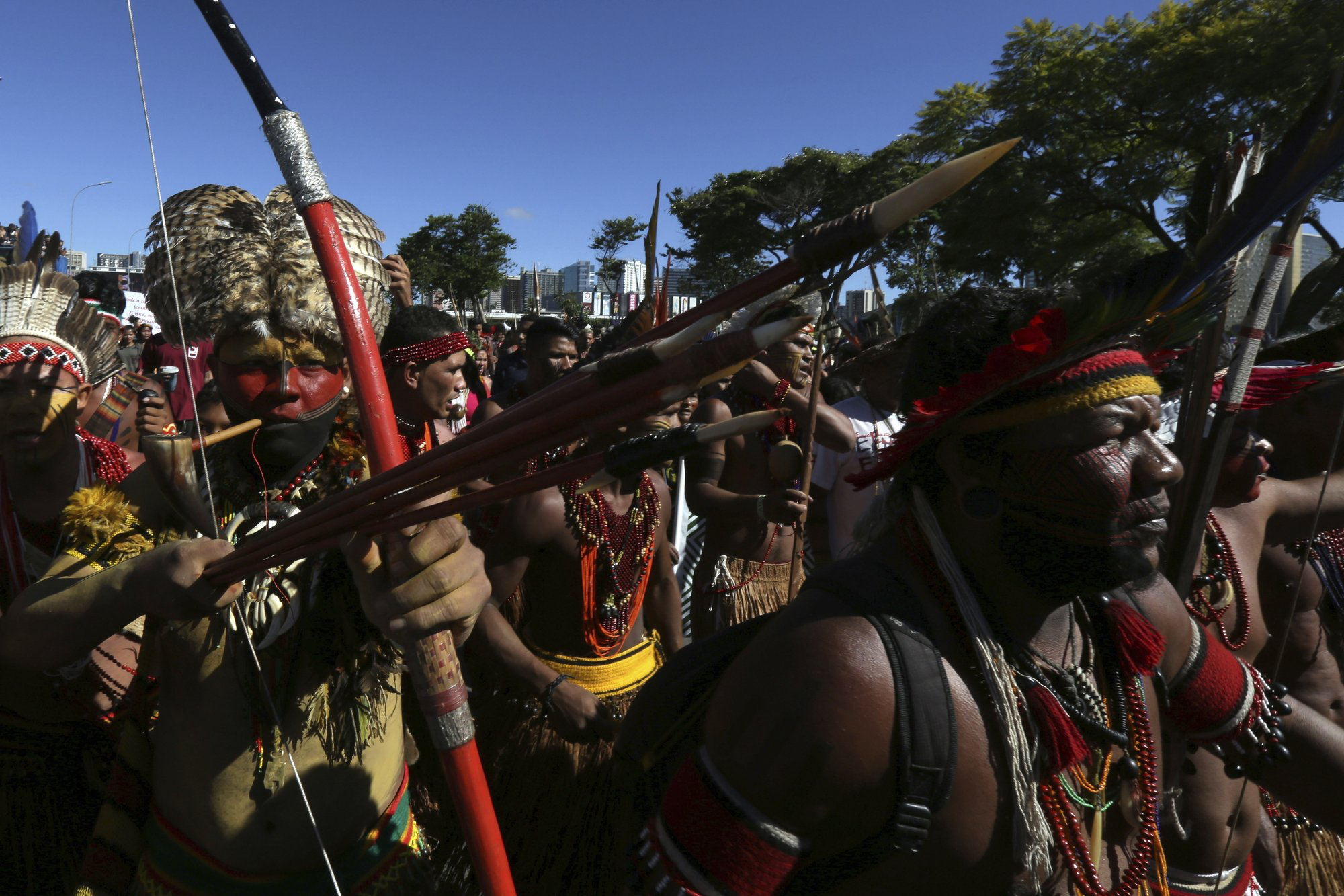Indigenous Pataxo men carry their weapons during the Free Land Camp protest in Brasilia on Friday, April 26. The march protests the rollbacks of indigenous land and rights under Bolsonaro. Photo:  AP Photo /Eraldo Peres.