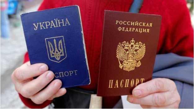 A woman holds up her blue Ukrainian passport (left) and new red Russian passport (right) in Simferopol, Crimea, after Russia formally granted Crimeans Russian citizenship after seizing the peninsula in 2014. Photo:  Reuters