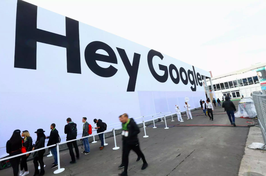 People gathered outside of a Google billboard highlighting the company's signature smart home phrase. Photo: Dave Gershgorn /  Quartz