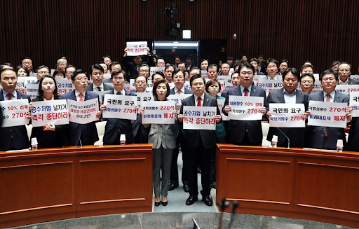 LKP members hold signs criticizing the decision to fast-track bills at the National Assembly after an emergency party meeting on April 23, 2019. Photo:  Yonhap