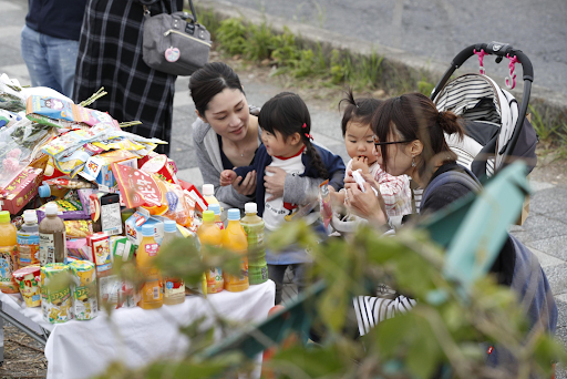 People pay respects at a makeshift memorial on Thursday, May 9, 2019, to the victims of the two-car collision that claimed two lives and injured over a dozen others the day prior. Photo:  KYODO