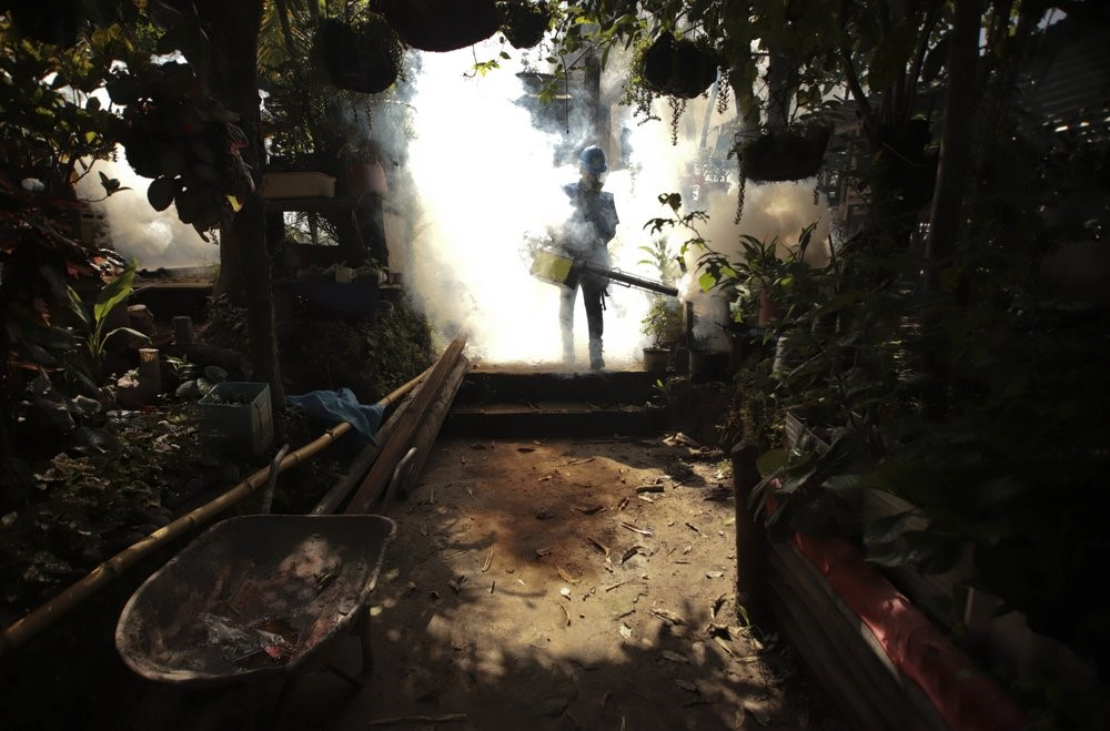 A worker fumigates inside a home in an attempt to control the spread of the mosquito-borne disease in El Salvador. Photo:  AP / Salvador Melendez