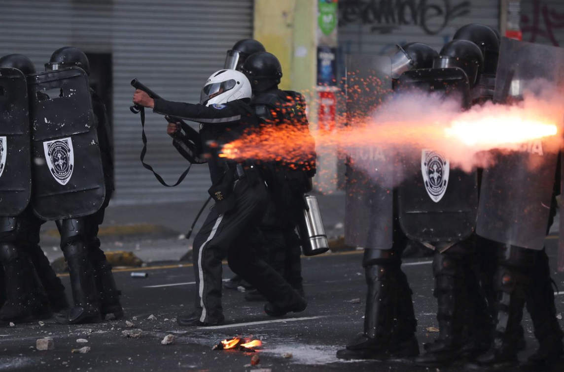 Members of the riot police aim their weapons as they clash with demonstrators during protests. Photo:  Ivan Alvarado/REUTERS