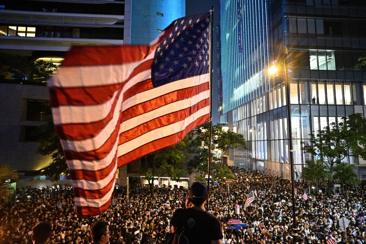 A man waves an American flag at a protest rally in Hong Kong. Photo:  AFP