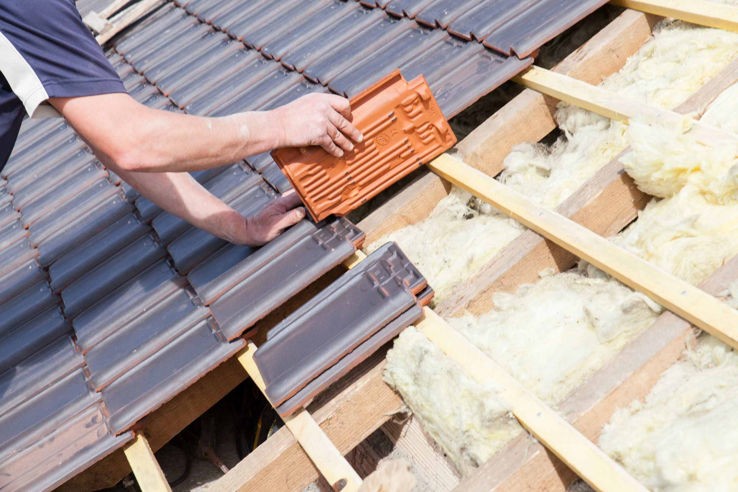 Man laying new tiles on roof