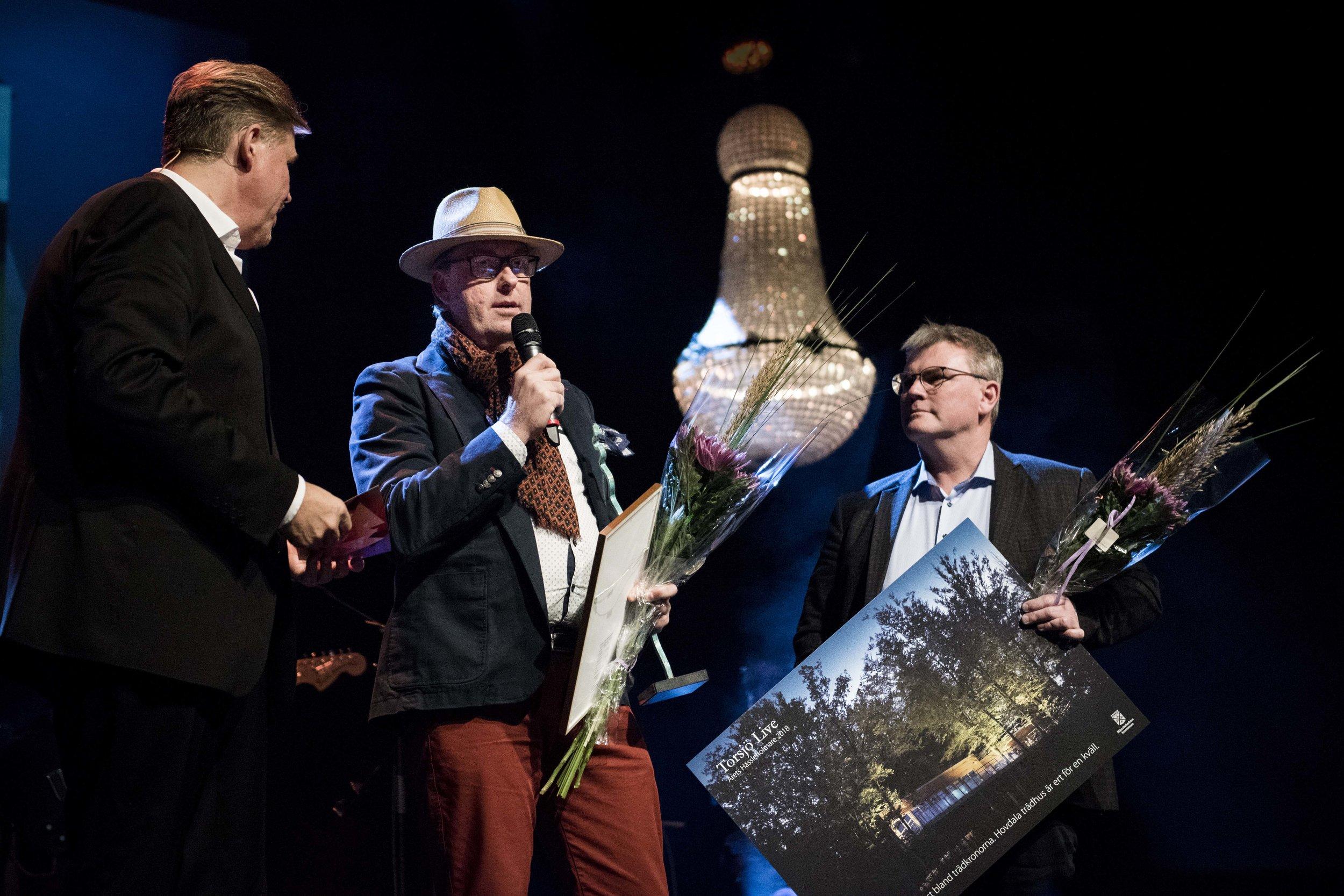 """Mats Gunnarsson (i mitten) och Jonas Johansson (till höger) tilldelas priset """"Årets Hässleholmare"""" på Hässleholmsgalan 2018."""