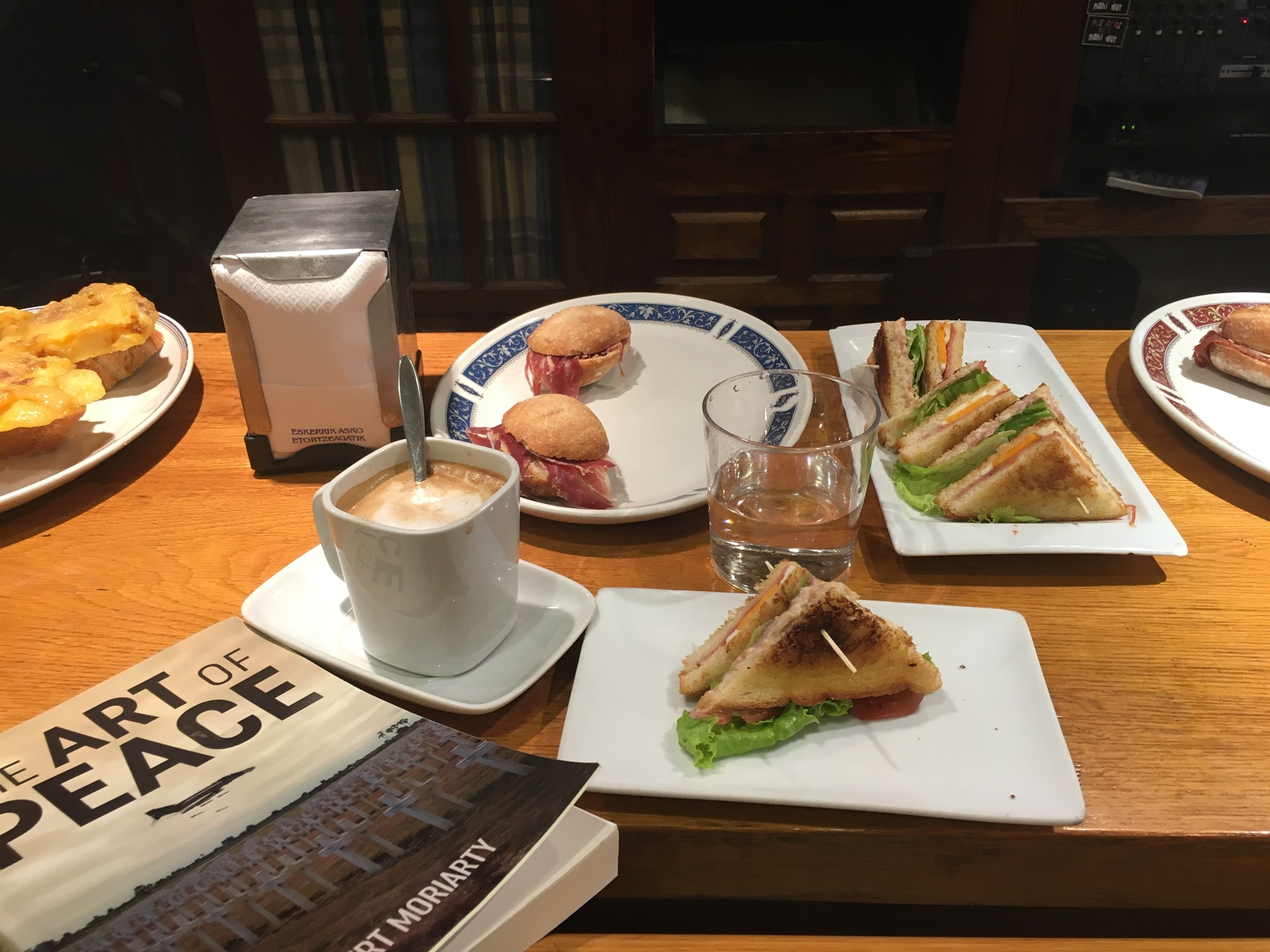 The perfect breakfast; - strong coffee, a fresh glass of water, two pintxos and a somewhat pretentious book that aims at solving world peace. you give up after the intro and just enjoy life around you. the clatter of plates, chatter from the locals, blaring noise from the TV, traffic from outside.everything is just so... normal and you're part of the tapestry. you're one of the locals, immersed in the daily life, and yet you're a visitor for a few days, maybe a week or two, passing through. it's an oddly exciting feeling. But, the difference is that you're not a tourist. you're a local, someone who enjoys the small moments - and this is how the magic happens... how doors open.Pintxo is the Basque spelling of the Spanish Pincho, deriving from the verb