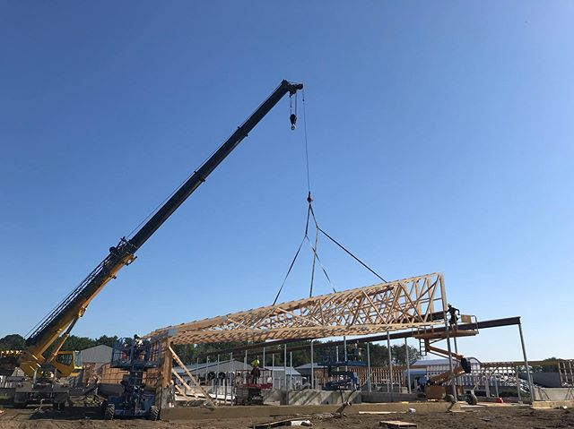 Placing rafter sections for a dairy barn.
