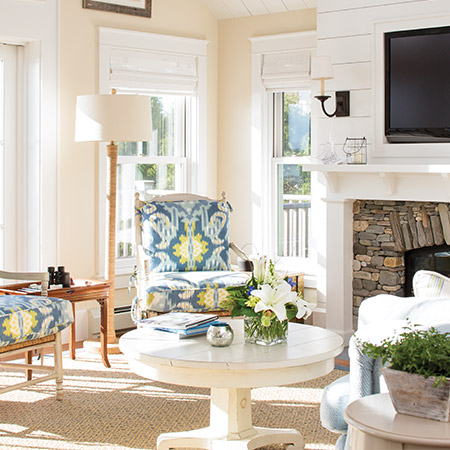 Hurlbutt Designs Pine Point Seaside Cottage renovation photo featuring a sun-lit living room with beautiful upholstered stairs.