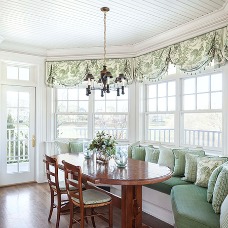 Hurlbutt Designs Kennebunk Traditional Beach Cottage New Construction photo featuring the dining room with custom window treatments and a built in seating area with custom upholstered pillows.
