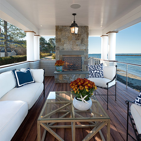 Hurlbutt Designs Modern Coveside Cottage photo of porch with beautiful outdoor furniture and fireplace and gorgeous ocean views.