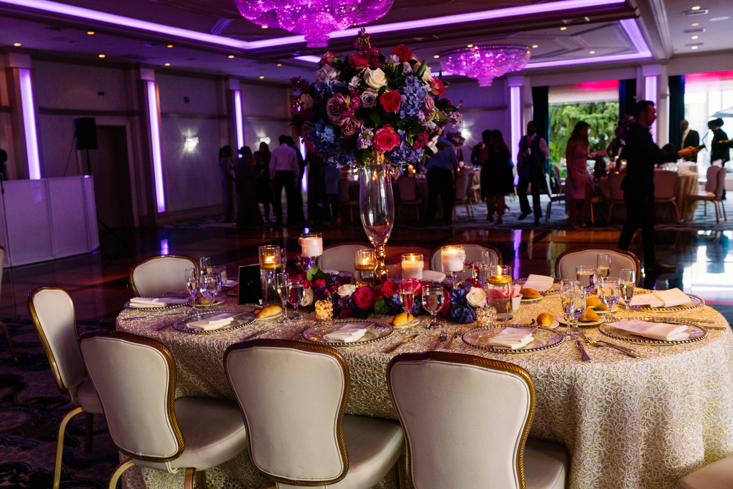 New York City Summer Wedding, Shades of Purple and Pink Flowers set on a large centerpiece with candles every where.  Linens provided by The Finishing Touch New York