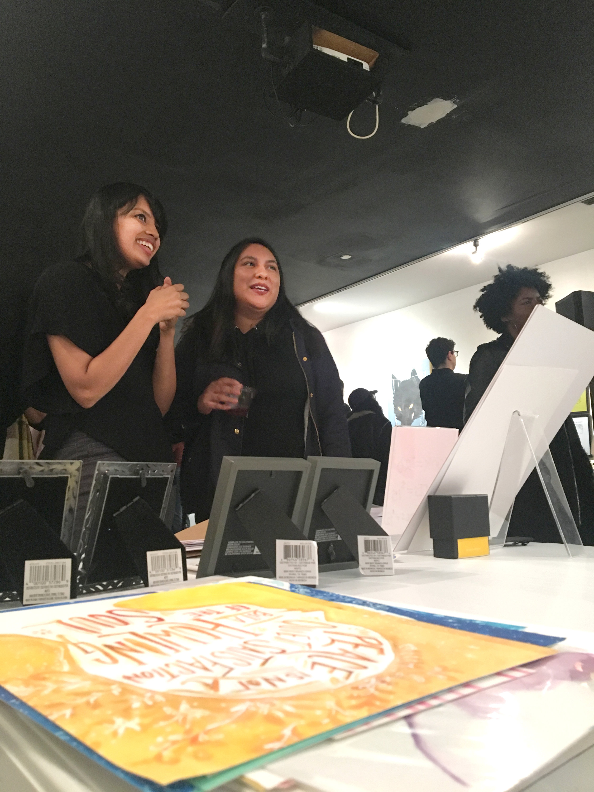 Artist enthusiastically shares her work to a gallery visitor