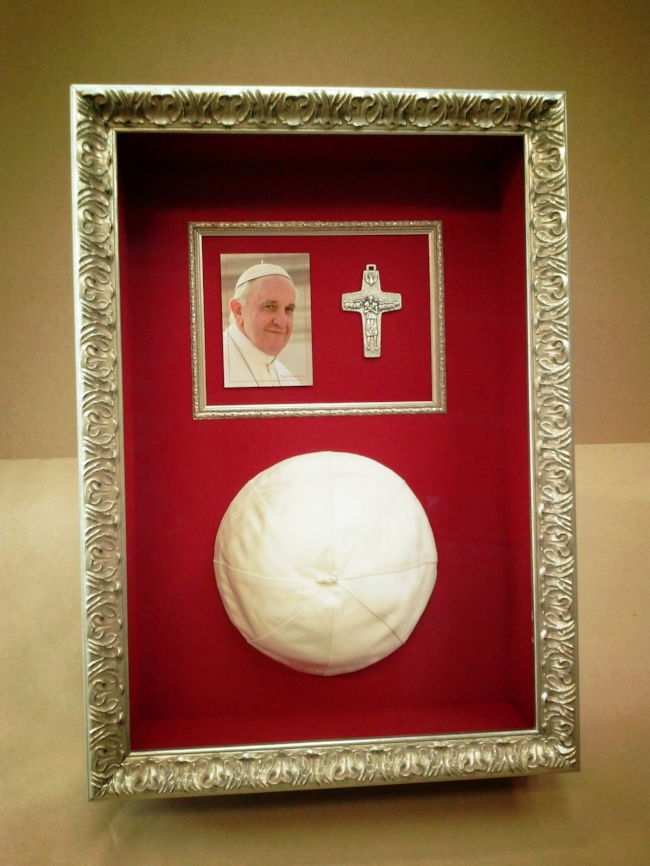Papal Beanie In Gilded Silver Frame and Museum Glass - The client wanted to preserve memories of a trip to Rome and an audience with the Pope. We chose a deep silver gilded frame to reflect the opulence of the Vatican and to accommodate the 4