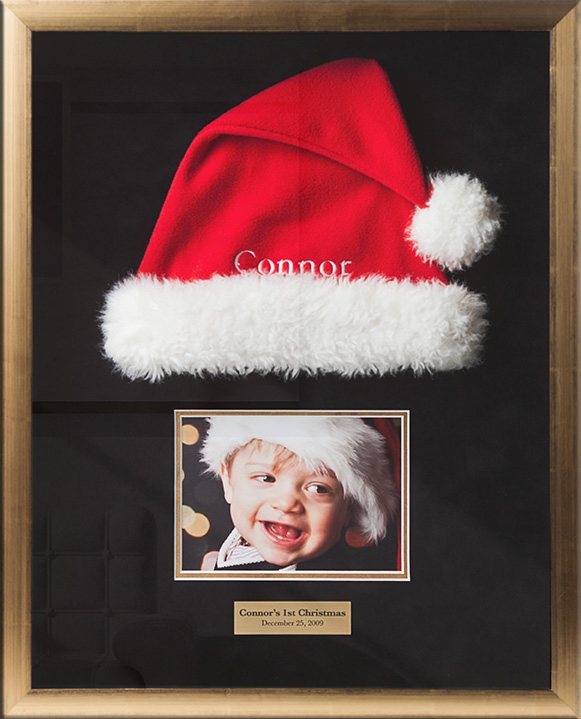 Baby's First Christmas in a Custom Frame - Shadowboxes are a perfect way to preserve special memories, like baby's first Christmas, Hanukah, or birthday. A brushed brass plaque matches the gold toned frame, but the focus is a great expressive photo of this happy boy, and the actual hat he wore to meet Santa.