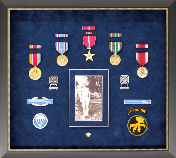 Custom-Framed Military Service Medals: A Fitting Tribute - A group of medals, pins, and patches commemorate a lifetime of military service. A photo in uniform completes the theme of this heirloom piece, framed in polished wood with a gold accent and deep blue suede matting.