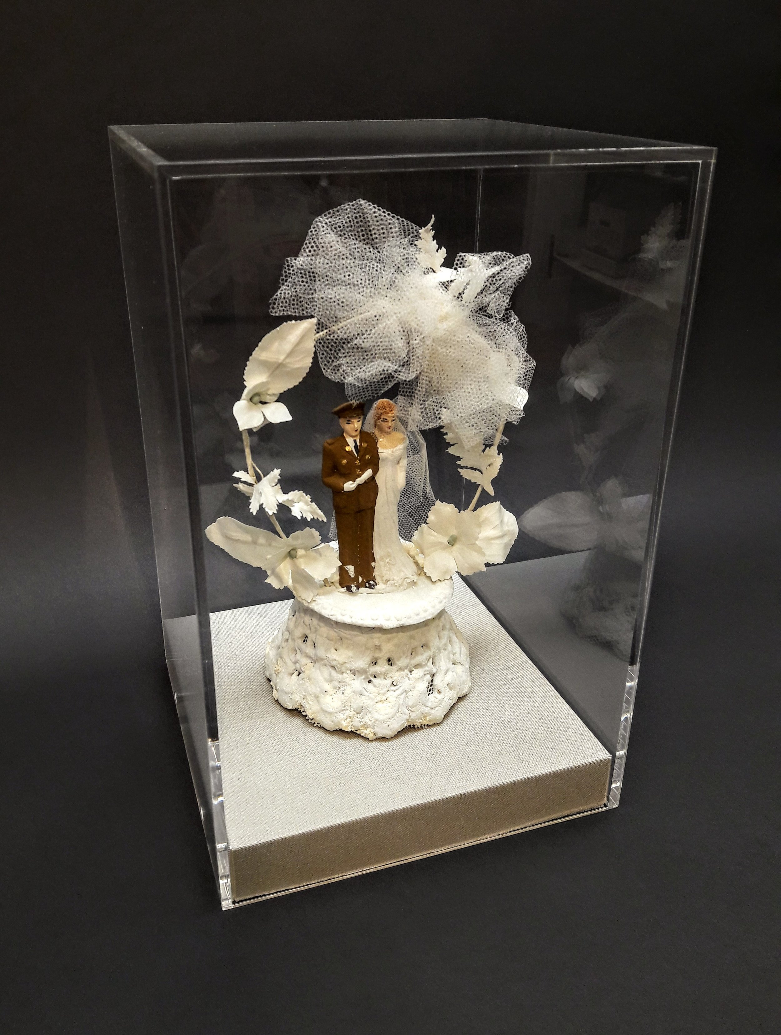 Vintage Cake Topper in Acrylic Box - A clear acrylic display box is a great solution for special objects like this vintage cake topper. We designed a linen platform and hidden mount to give it stability.