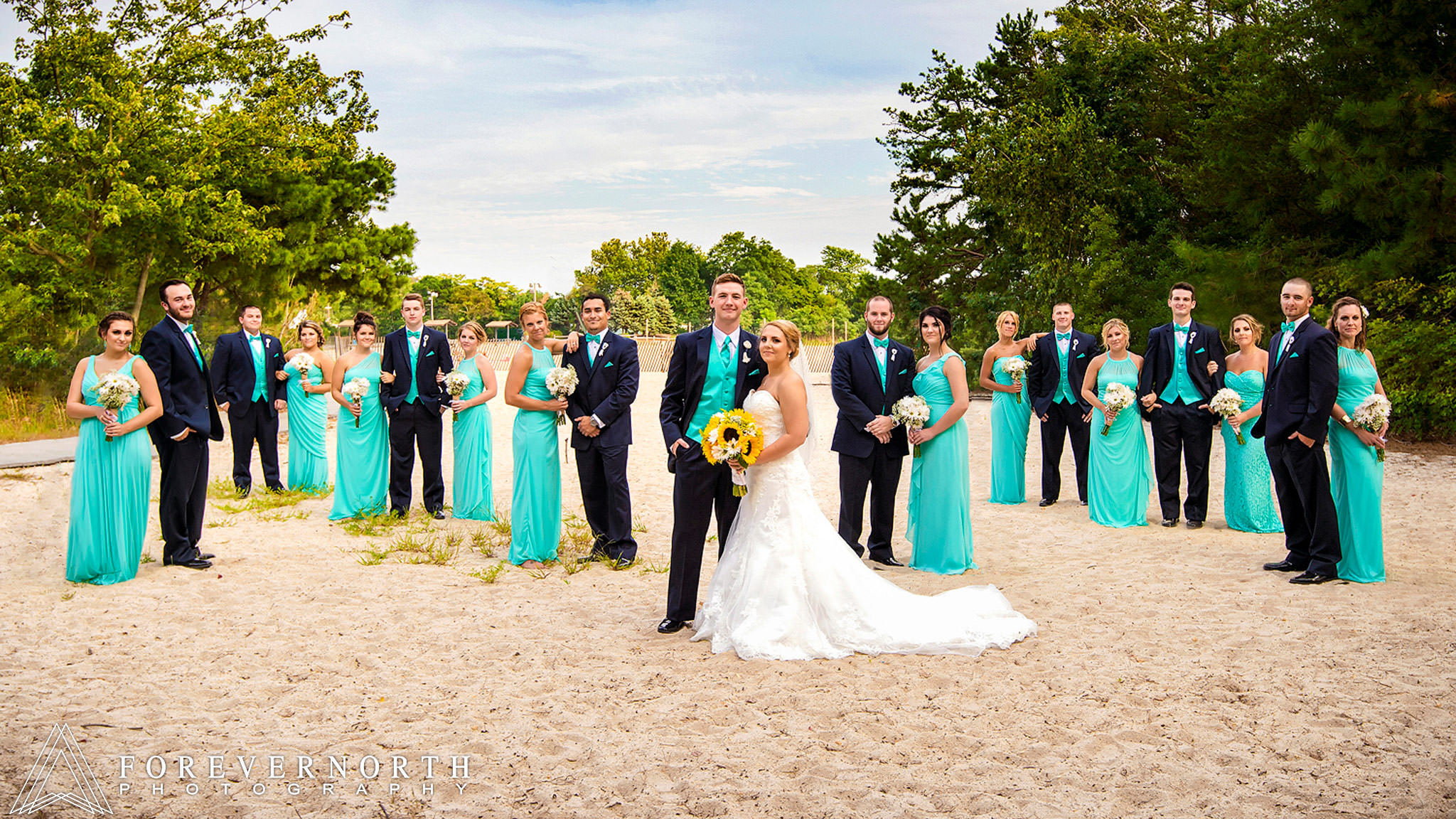 Bridal party group shot posed on the beach at windward park