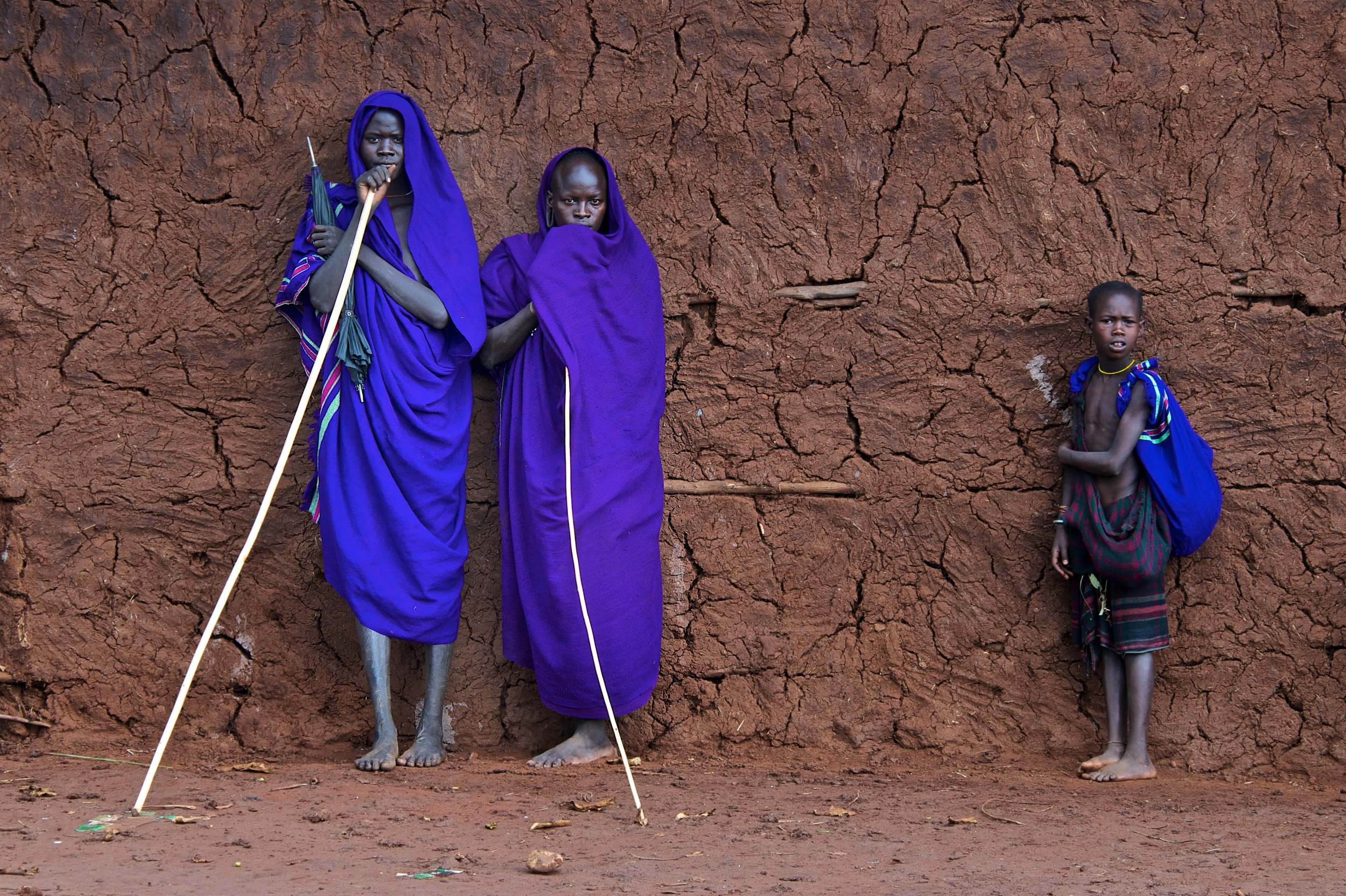 Two African ladies and a child wearing purple clothes