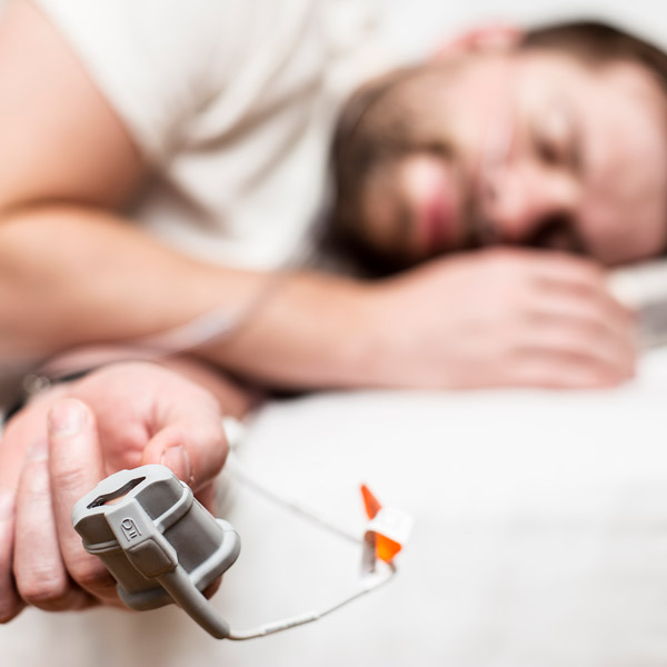 Man sleeping with blood oxygen tester on finger.