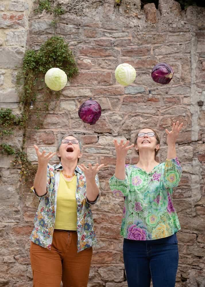 Katie and Jo tossing cabbages in the air