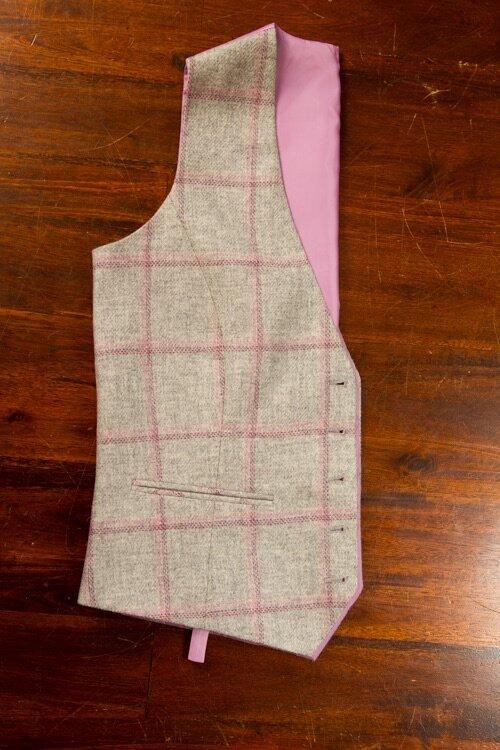 - Tweed Dames Vest Gilet Grijs met een roze ruit.