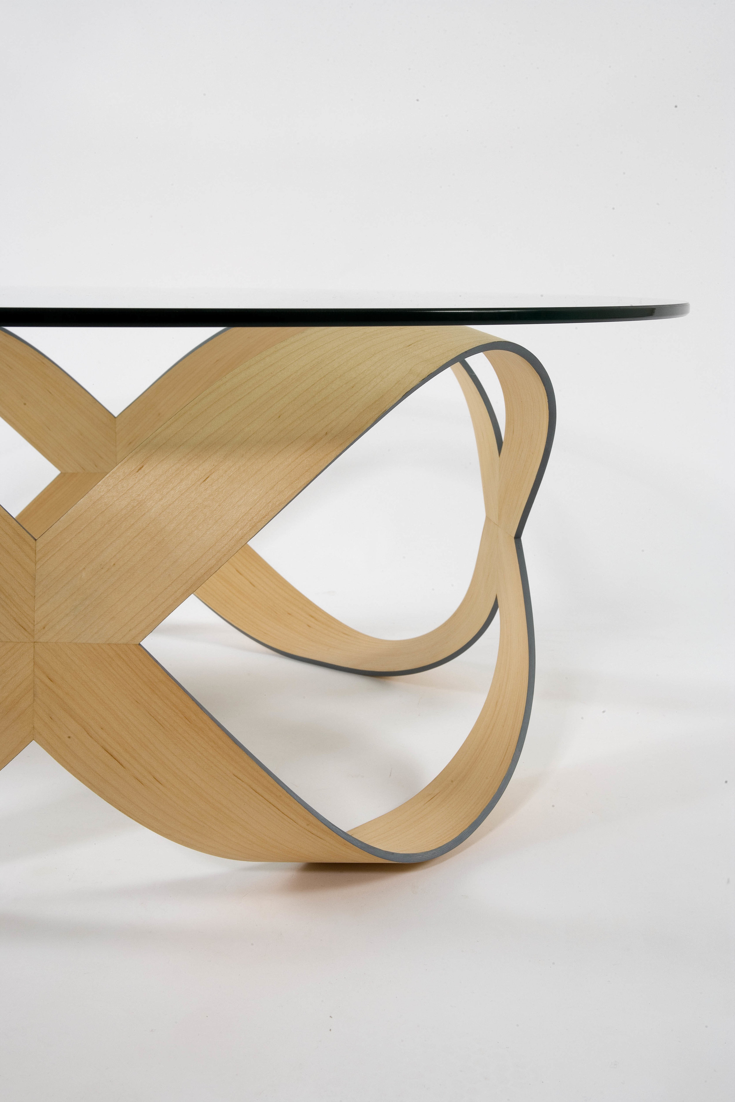 'Infinity squared' coffee table - 'Infinity Squared' is a development of the multi-award winning 'Infinity + 1' table. It offers the same intrigue and beauty through its elegant, flowing lines but is smaller in size and has a character of its own.Designed to be a piece of functional sculpture, the table is contemporary in style but capable of sitting in many environments thanks to its relaxed, harmonious form. The aesthetic simplicity of 'Infinity Squared' masks its complex construction and the deceptive strength of such a slight structure.Available in American Black Walnut, Maple, Sweet Chestnut or Cherry as standard, other timbers, including coloured veneers, are possible but may incur a small surcharge. Edge colours can be matched to specific colours or existing décor.Dimensions: Height 32.5cm, diameter 87.5cmPrice: £2400