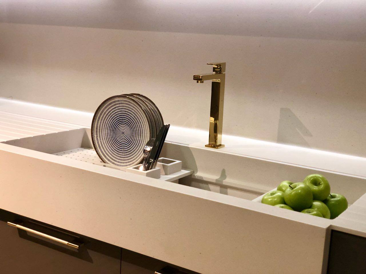 Cream coloured Corian worktop and integrated sink with gold tap. Plates stacked to left of sink with green apples on the right.
