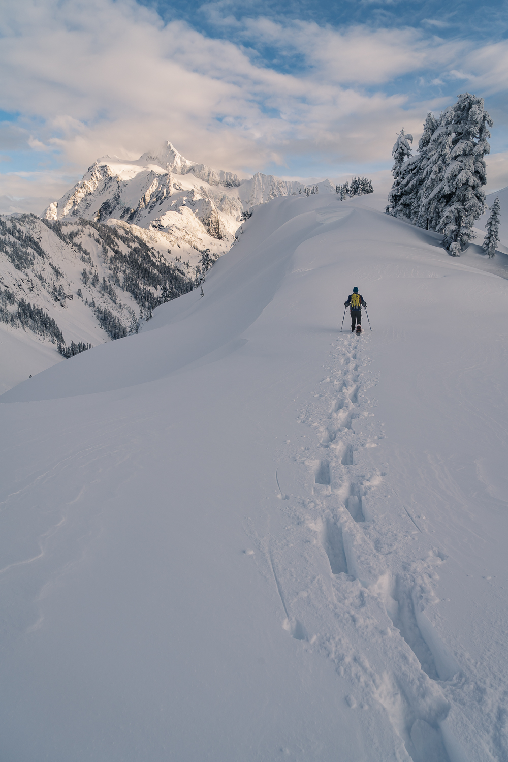 Becca snowshoes up the last hundred yards towards Huntoon Point, with a spectacular view of Mount Shuksan covered in snow.