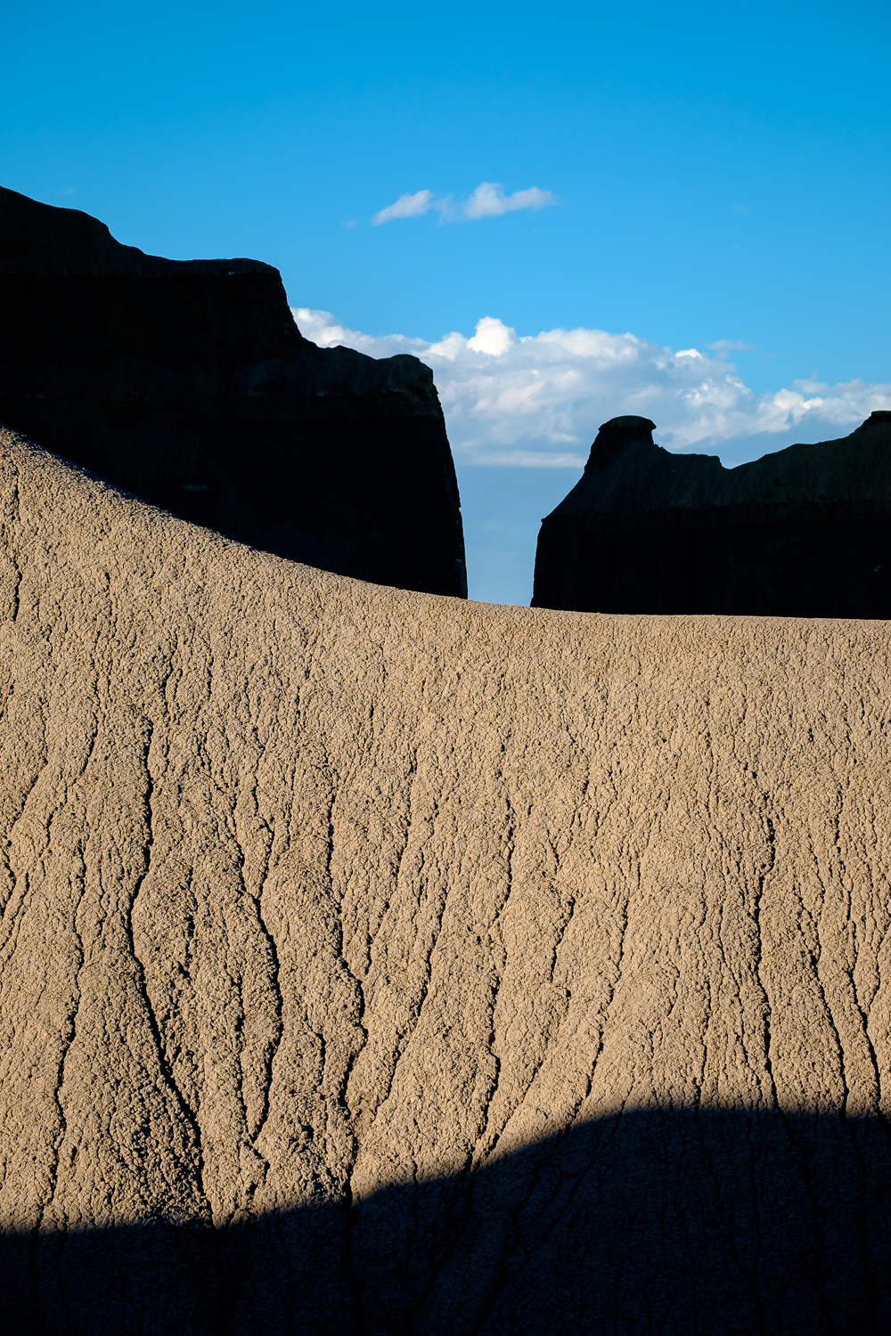 Sunlight and shadows play on the eroded forms of the Cainville Badlands, in Utah.
