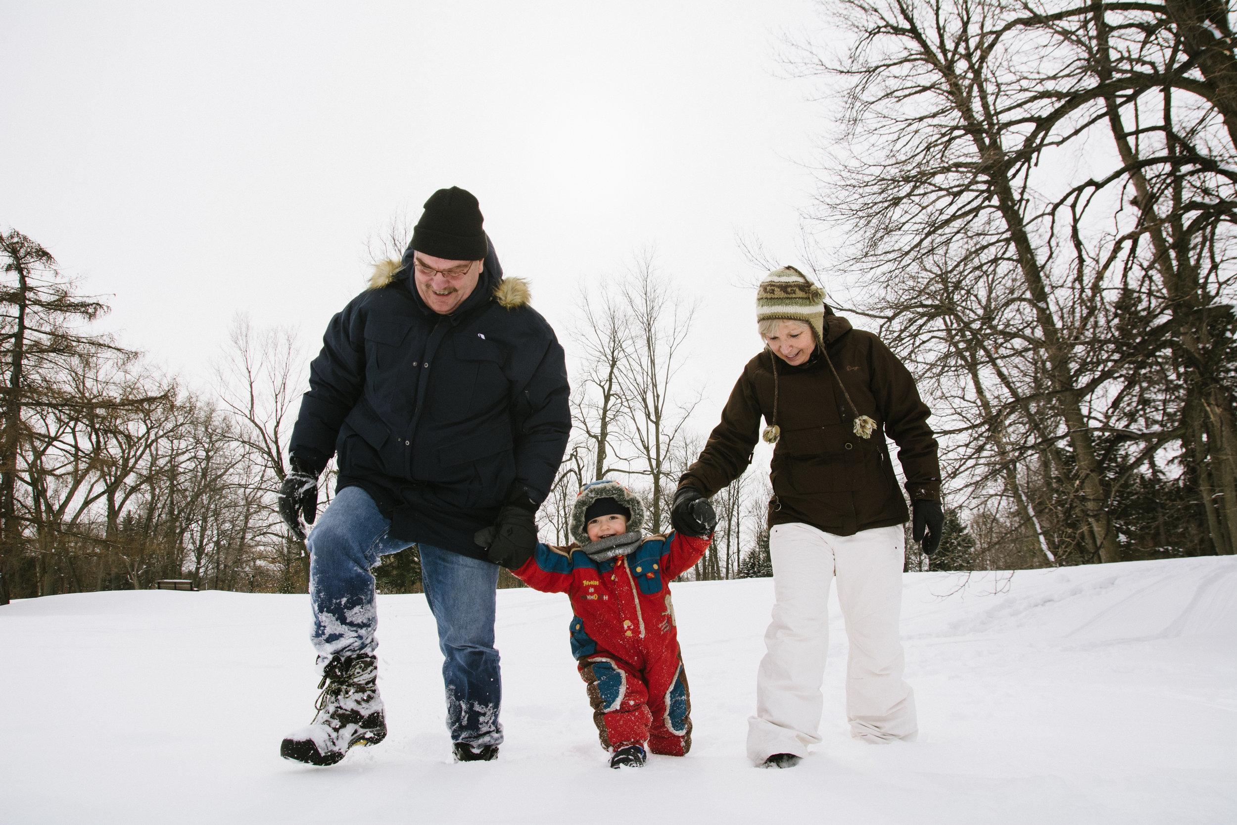 photo-d-un-enfant-en-habit-de-neige-avec-ses-grands-parents-l-hiver-a-montreal-photographe-enfant-famille-montreal.jpg