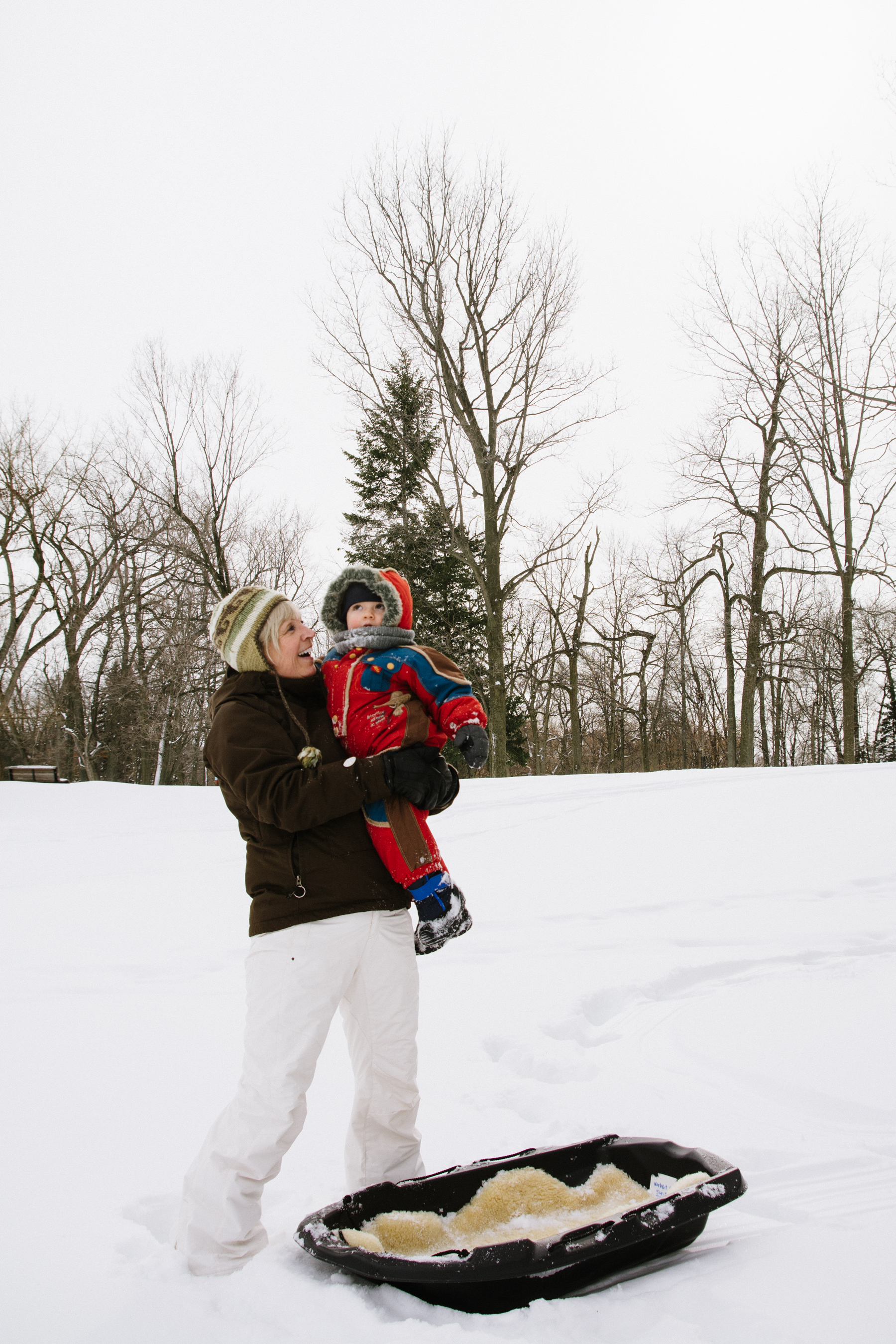 photo-d-une-grand-mere-avec-un-enfant-en-habit-de-neige-dans-les-bras-l-hiver-a-montreal-photographe-enfant-famille-montreal.jpg