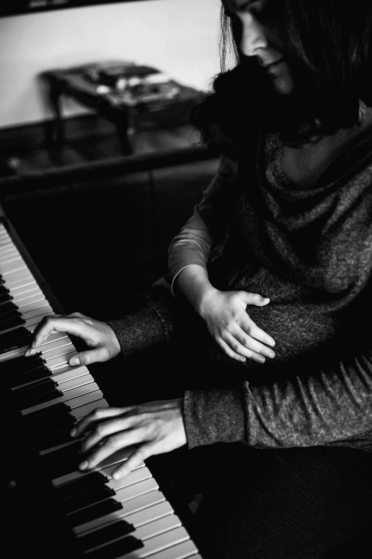 photo-noir-et-blanc-une-femme-enceinte-qui-joue-du-piano-avec-sa-grande-fille-photographe-maternite-bebe-famille-montreal.jpg