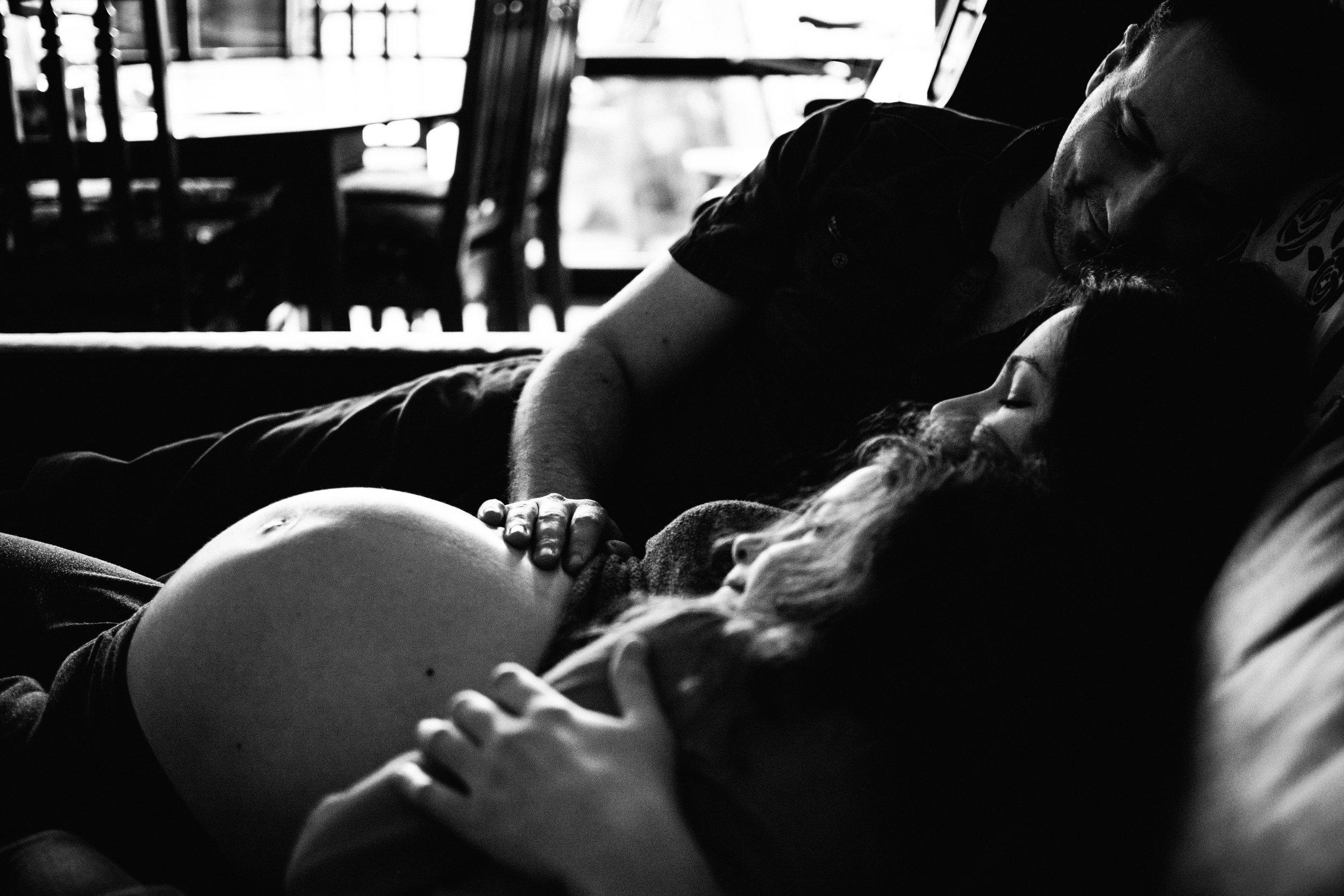 photo-noir-et-blanc-d-une-famille-qui-atteint-la-venue-d-un-petit-frere-sur-le-divan-photographe-maternite-bebe-famille-montreal.jpg