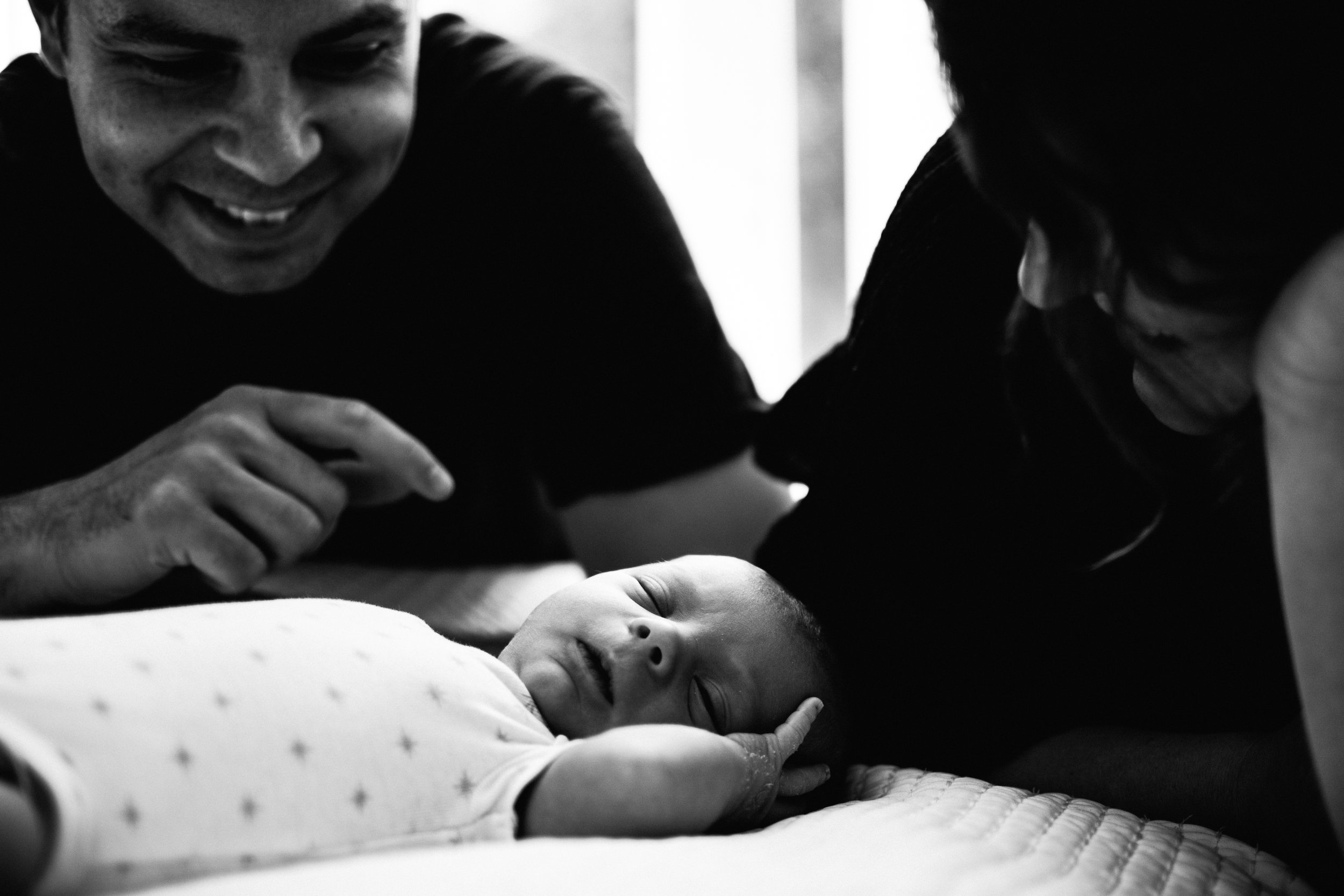 photo-noir-et-blanc-dun-nouveau-ne-et-ses-parents-sur-un-lit_photographe-lifestyle-famille-montreal.jpg