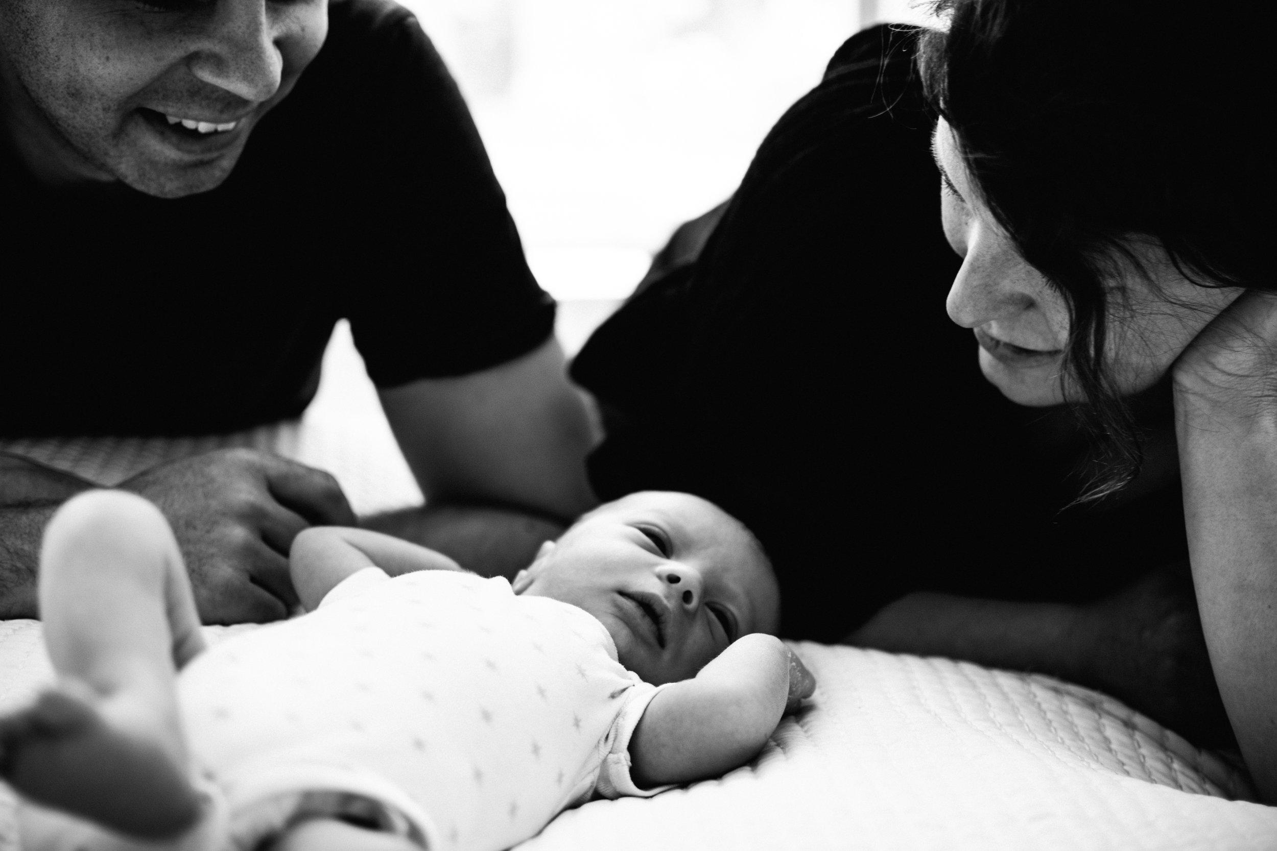 photo-noir-et-blanc-dun-nouveau-ne-et-ses-parents-sur-un-lit_photographe-lifestyle-famille-montreal-4.jpg