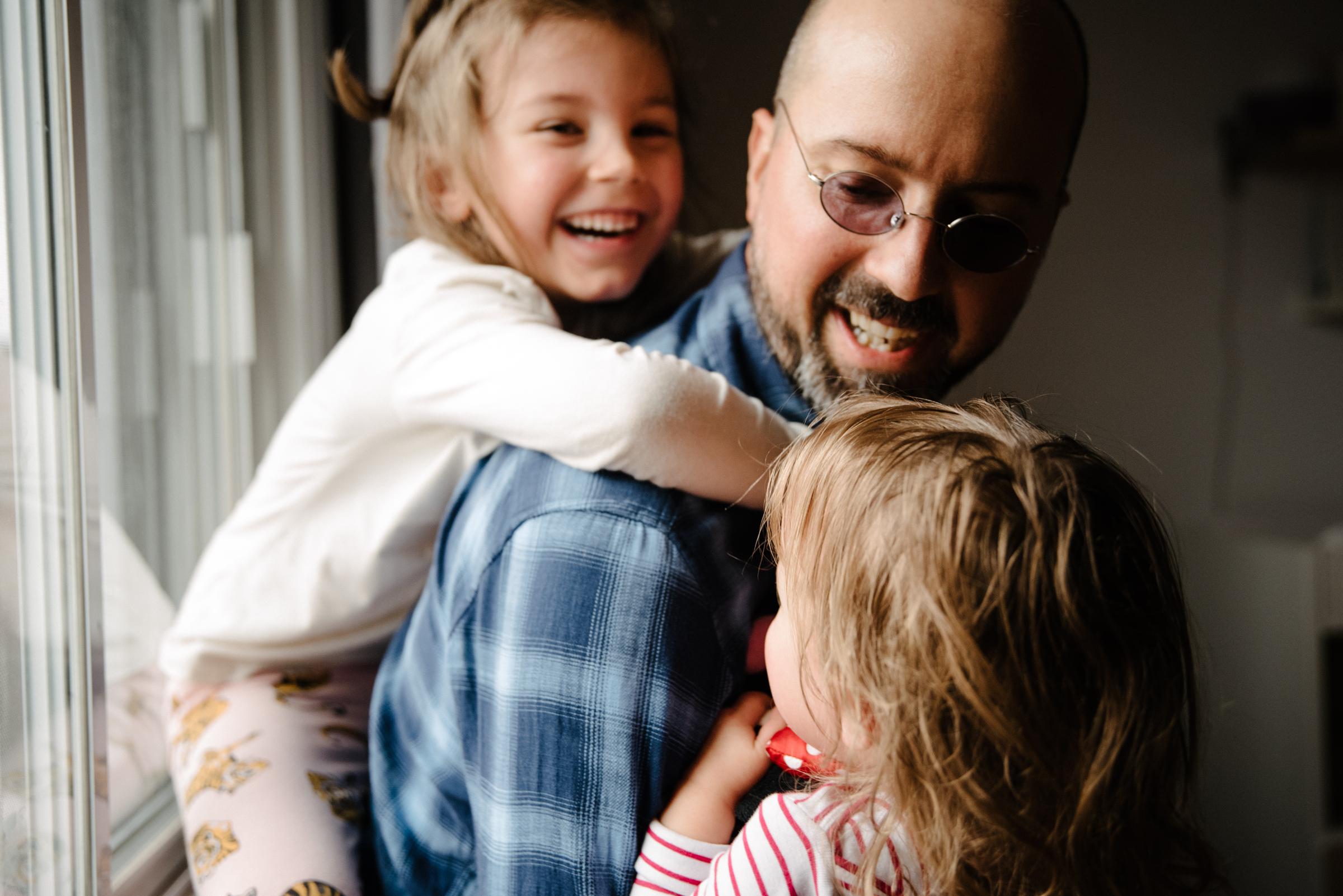 005-photo-d-un-papa-heureux-qui-rit-avec-ses-deux-grandes-filles-photographe-de-famille-lifestyle-a-montreal-761.jpg