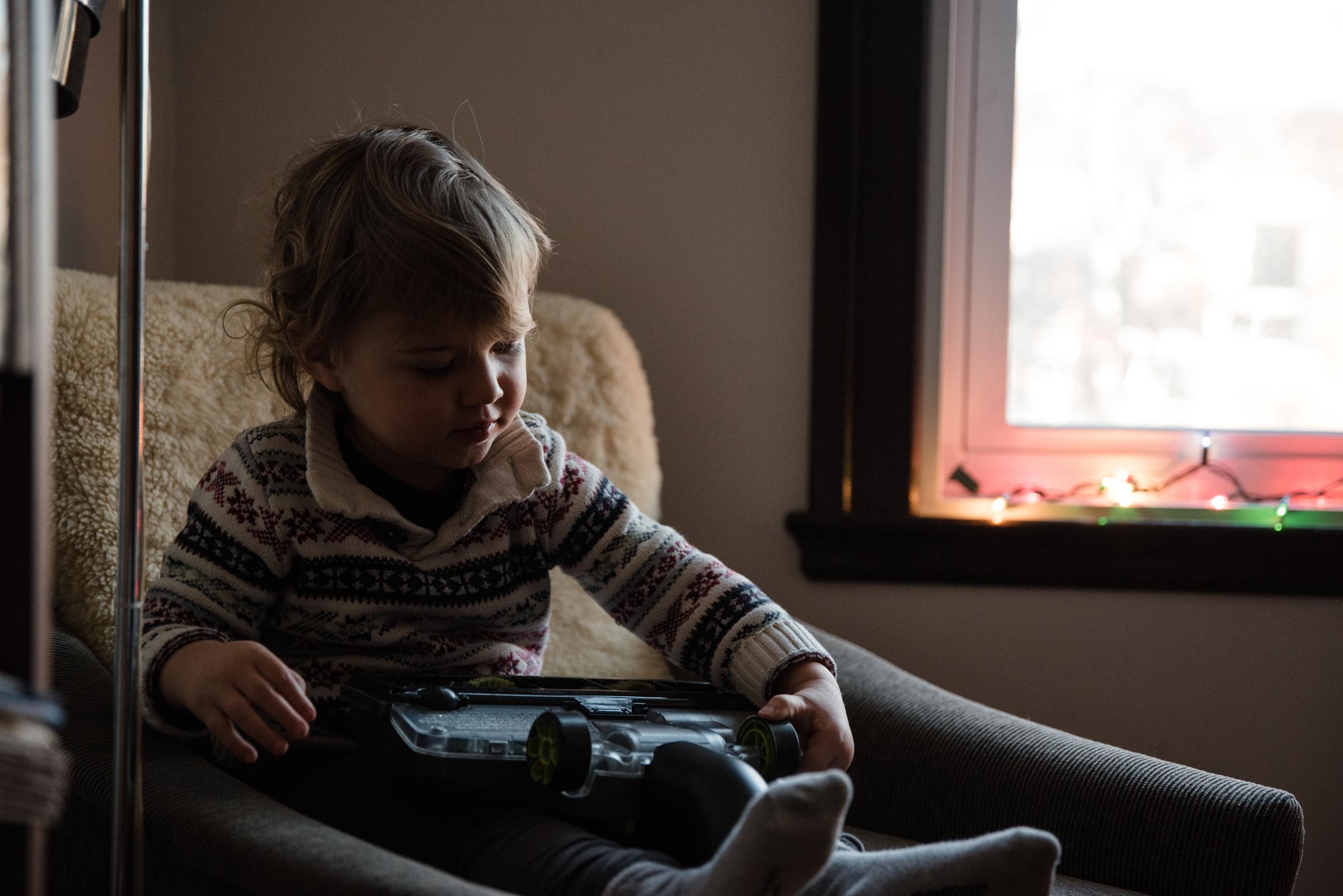 013-photo-d-un-enfant-qui-joue-avec-la-tete-dune-balayeuse-a-tapis-photographe-lifestyle-famille-a-montreal-1225.jpg
