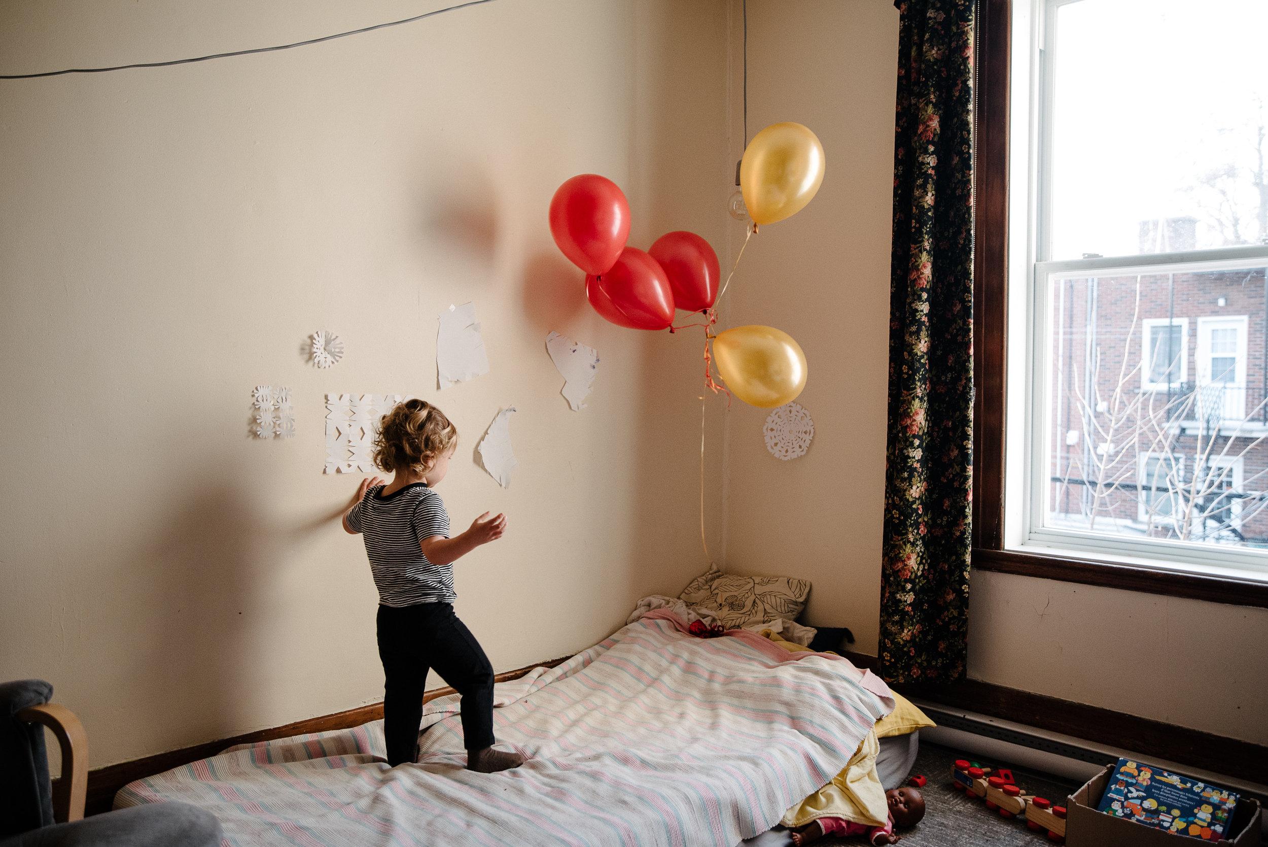 020-photo-dun-enfant-jouant-avec-un-bouqet-de-ballons-flottants-debout-sur-son-lit-photographe-lifestyle-famille-a-montreal-1423.jpg
