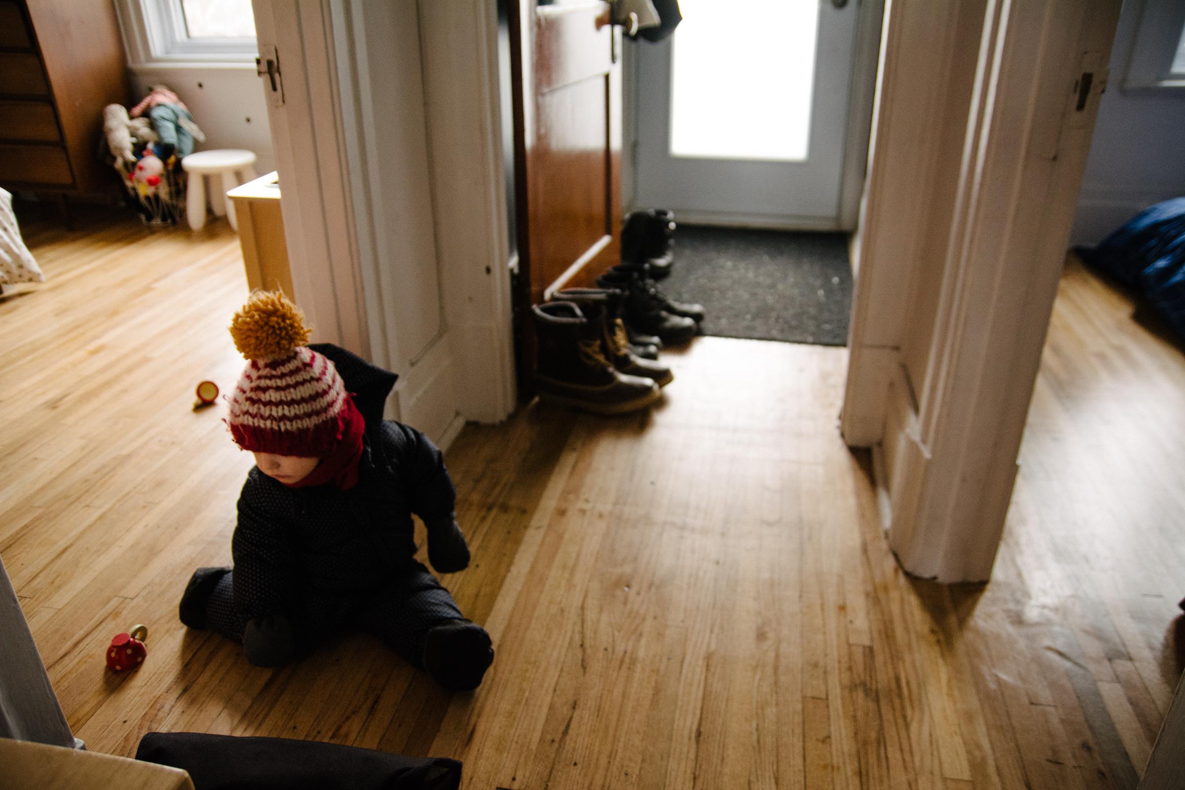 photo-d-un-enfant-dans-son-habit-de-neige-assis-dans-lentree-photographe-famille-lifestyle-a-montreal-118.jpg